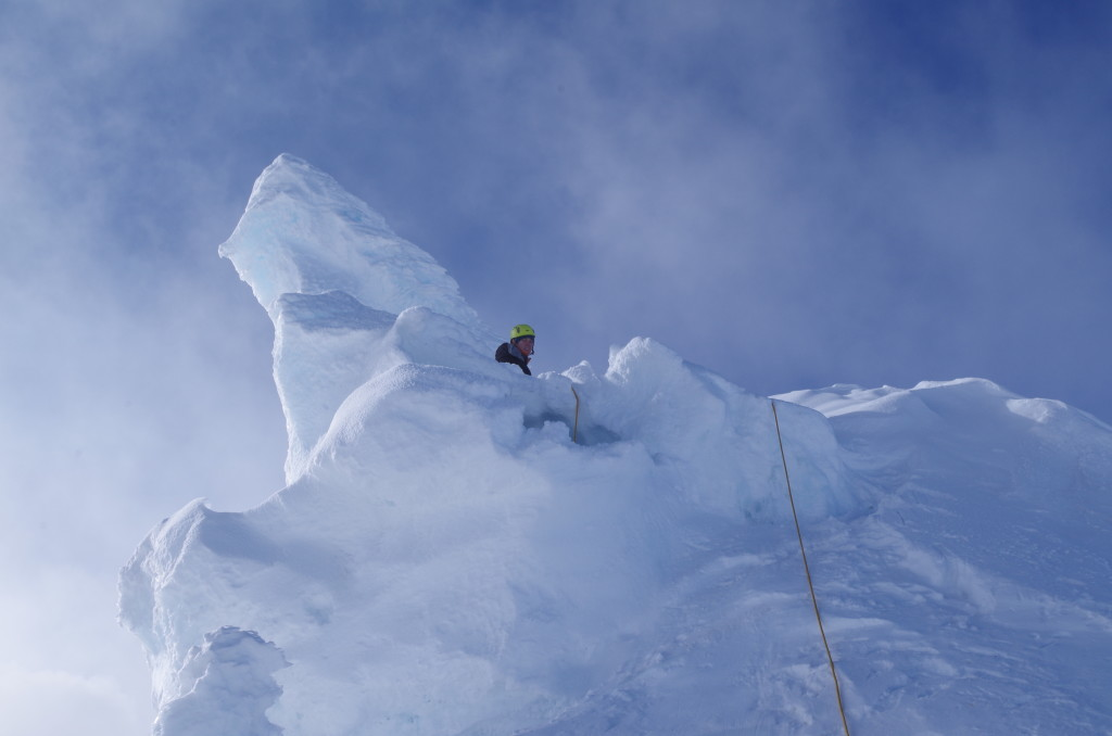 Heroin Tower: Lyra has set up an anchor above the entrance (the small hole into which the ropes disappear). She has already belayed Tobias into the tower, and I'm about to follow. We climb up to the edge and then in, wearing crampons and using ice axes.